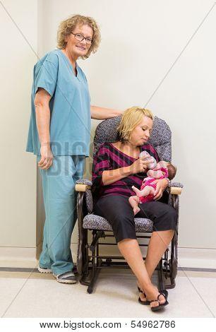 Full length portrait of nurse standing by mother feeding newborn babygirl in hospital