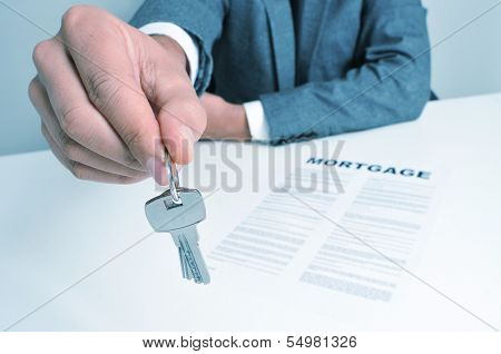 a man wearing a suit sitting in a desk with a mortgage contract giving a key ring to the observer