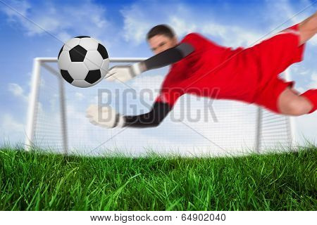 Fit goal keeper jumping up saving ball against field of grass under blue sky poster