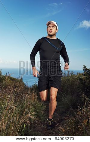 fitness running man on mountain trail near ocean exercising for marathon training