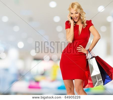 Happy smiling blond woman with shopping bags and mobile phone in shop interior