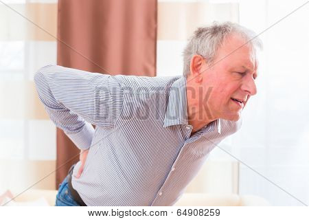 Old man holding back because of lumbago