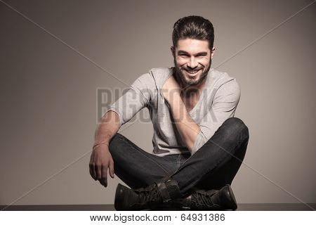 smiling young fashion man sits on the floor