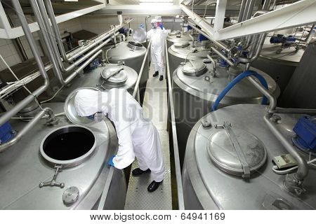 Two workers in white protective uniforms,mask and goggles working with industrial process tanks in plant