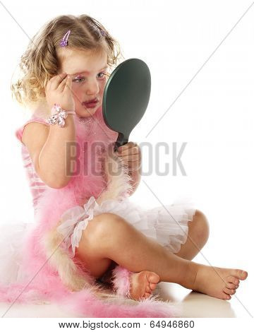 A beautiful little girl in a petticoat and boas applying her mommy's makeup on herself.