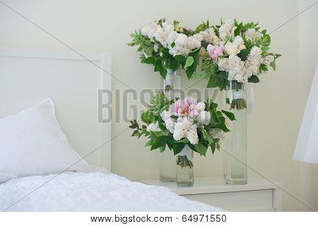 Flowers in vase on bedside table in bedroom. Fresh design.