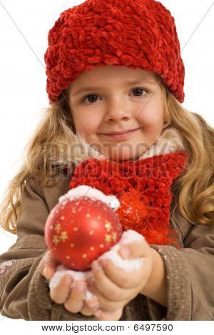 Little Girl Holding A Christmas Ball In Snow
