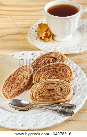 Bolo de rolo (swiss roll rollcake) typical Brazilian dessert cup of tea. Selective focus poster