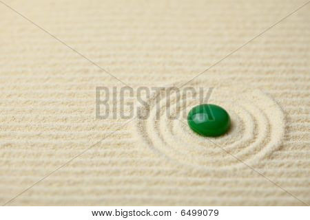Green Big Glass Drop On A Sand Surface