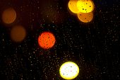 Raindrops on window at night in the city. Shallow depth of field poster