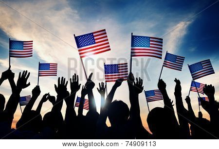Group of People Waving American Flags at Sunset