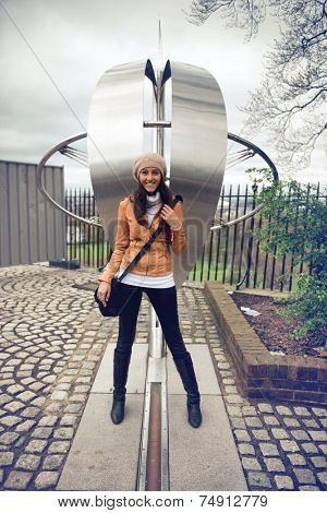 Smiling young woman tourist straddling the prime meridian line for zero degrees longitude at greenwich, London with one foot in the easter and one in the western hemisphere