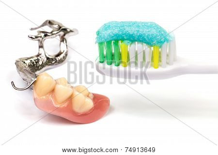 Oral Hygiene toothbrush with toothpaste and partial dentures on white background poster