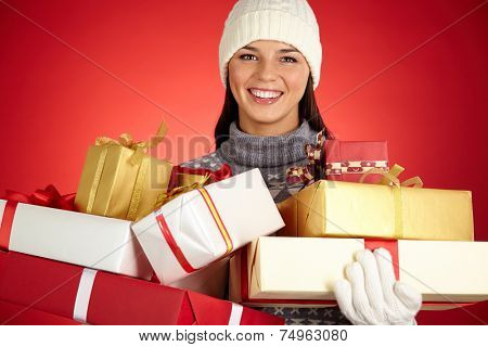 Cheerful young woman in winterwear holding wrapped xmas gifts