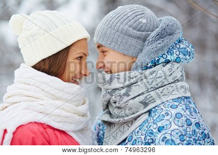 Profiles of happy dates in casual winterwear looking at one another
