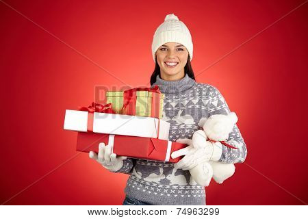Portrait of charming female in winterwear holding giftboxes and teddy bear