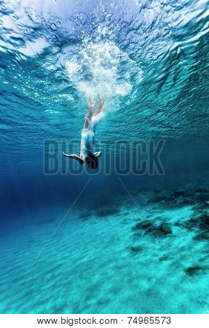 Active young female dancing underwater, enjoying summer vacation in blue transparent water, dive to the bottom of sea, enjoyment and freedom concept