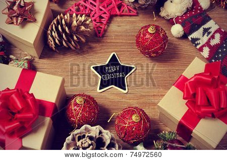 a pile of gifts and christmas ornaments, such as christmas balls and stars, on a rustic wooden table with a heart-shaped chalkboard with the text merry christmas in the center