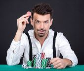 Portrait of a professional poker player sitting at a poker table with chips. poster