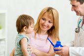 doctor counseling mother and boy about nasal irrigation or douche with neti pot poster