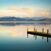 Wooden pier or jetty and on a blue lake sunset and cloudy sky reflection on water. Long exposure Versilia Massaciuccoli Lake Tuscany Italy. poster
