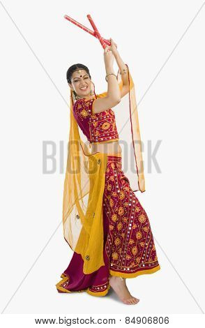 Woman in lehenga choli performing dandiya dance
