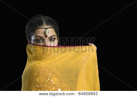 Close-up of a woman covering her face with chunni