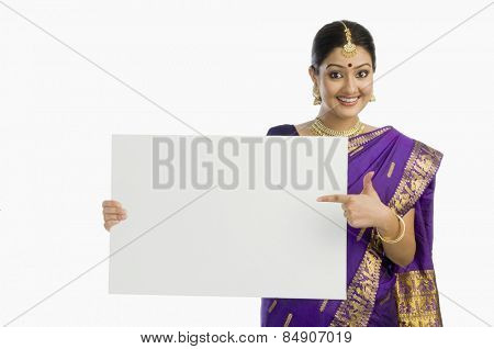 Beautiful woman in traditional Assamese dress holding a blank placard and smiling
