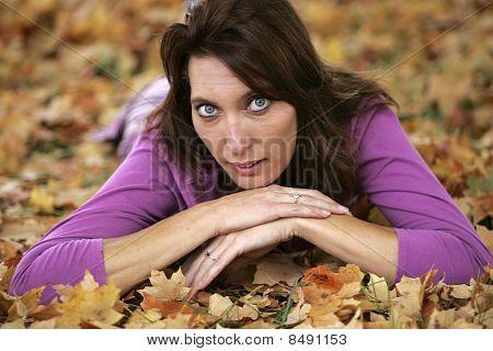Brunette Woman Lying In Leaves