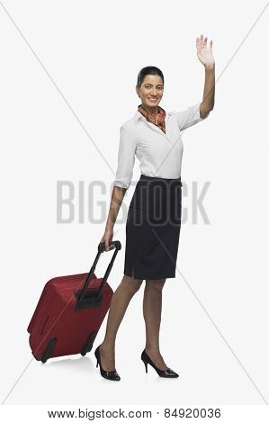 Air hostess carrying her luggage and waving poster