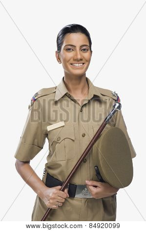 Portrait of a female police officer holding a stick and smiling