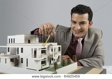 Architect with a model home in an office