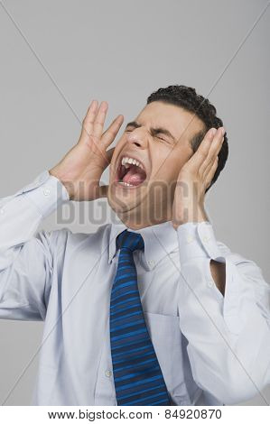 Businessman shouting with eye closed