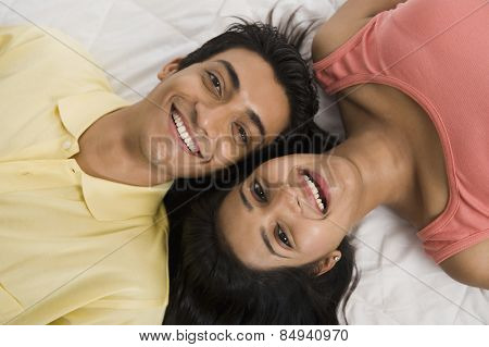 Close-up of a couple lying on the bed and smiling
