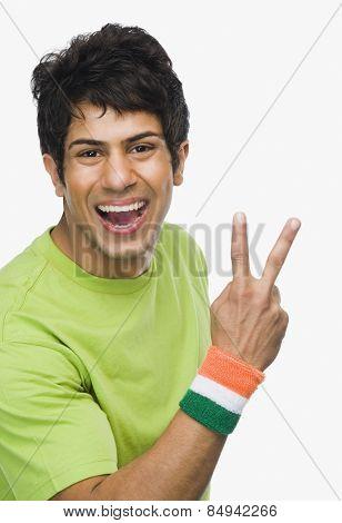 Portrait of a man showing peace sign