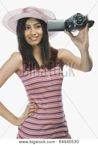 Close-up of a woman filming herself with a home video camera
