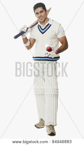 Portrait of a cricket batsman holding a bat and a ball