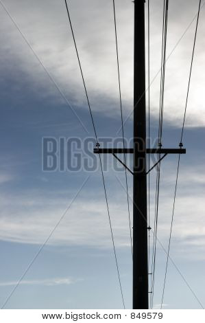 Power Lines And Pole Against Cloudy Sky