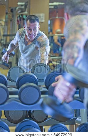 young man making dumbbell kickback - tricep exercise - at the gym - finish exercise - focus on the man face poster