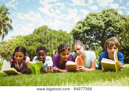 Portrait of children lying on grass and reading books at the park