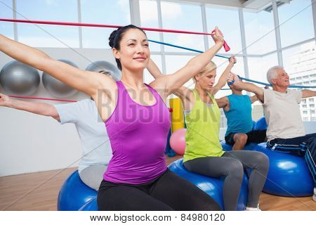 Fit people on fitness balls exercising with resistance bands in gym