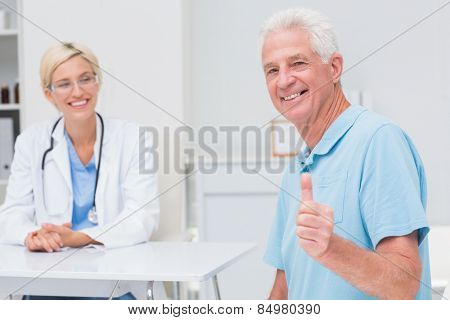 Portrait of happy senior patient gesturing thumbs up while doctor looking at him in clinic