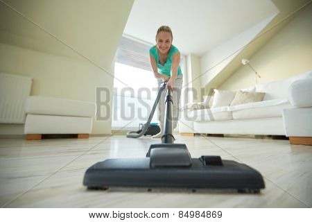 people, housework and housekeeping concept - happy woman with vacuum cleaner at home