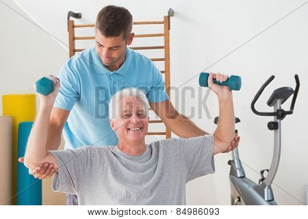 Senior man working out with his trainer in fitness studio