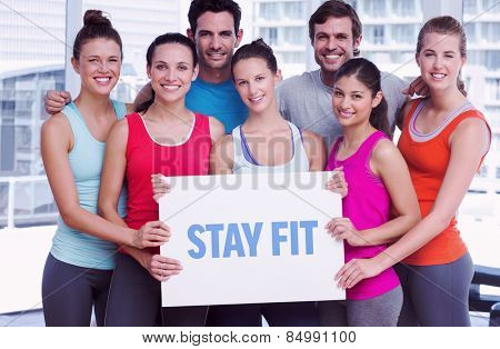 The word stay fit against fit smiling people holding blank board