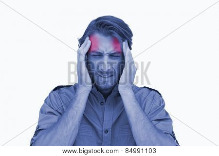 Man wincing with pain of headache on white background