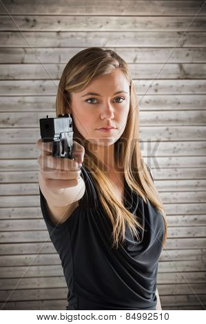 Femme fatale pointing gun at camera against wooden planks background