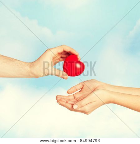 love, relationship, charity and medicine concept - man hand giving red heart to woman