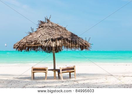 Two deck chairs and umbrella on tropical beach.