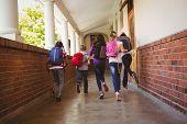 Full length rear view of school kids running in school corridor poster